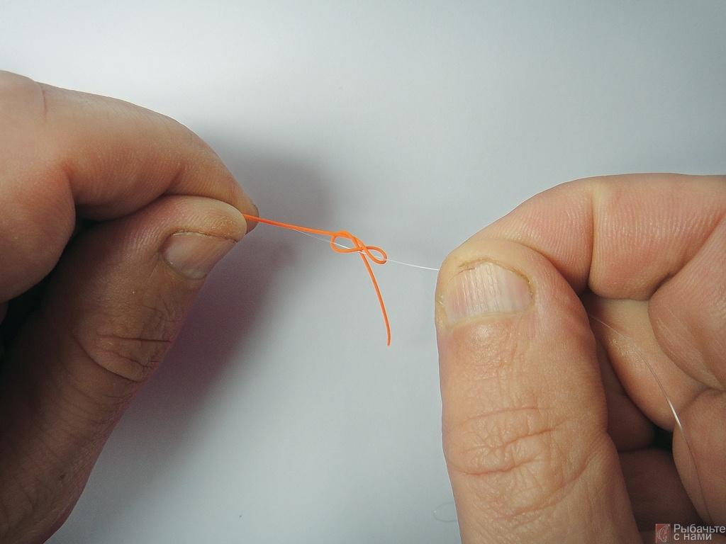 Свободный конец резинового жгута зафиксируйте стопорным узлом на флуорокарбоне.