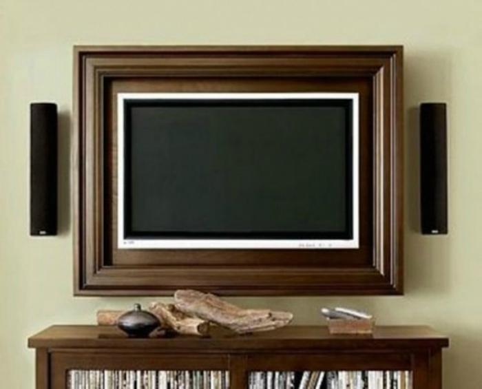 Плоский телевизор в раме из темного дерева добавит комнате элегантности и изысканности.