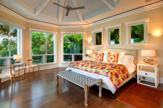 Интерьер угловой спальни с округленными стенами и множеством окон