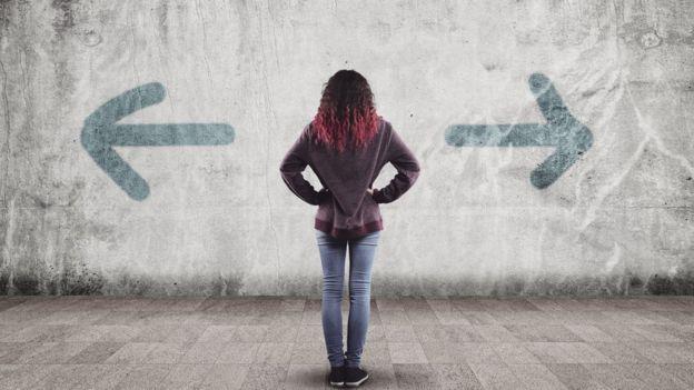 Женщина смотрит на стрелки в разные стороны