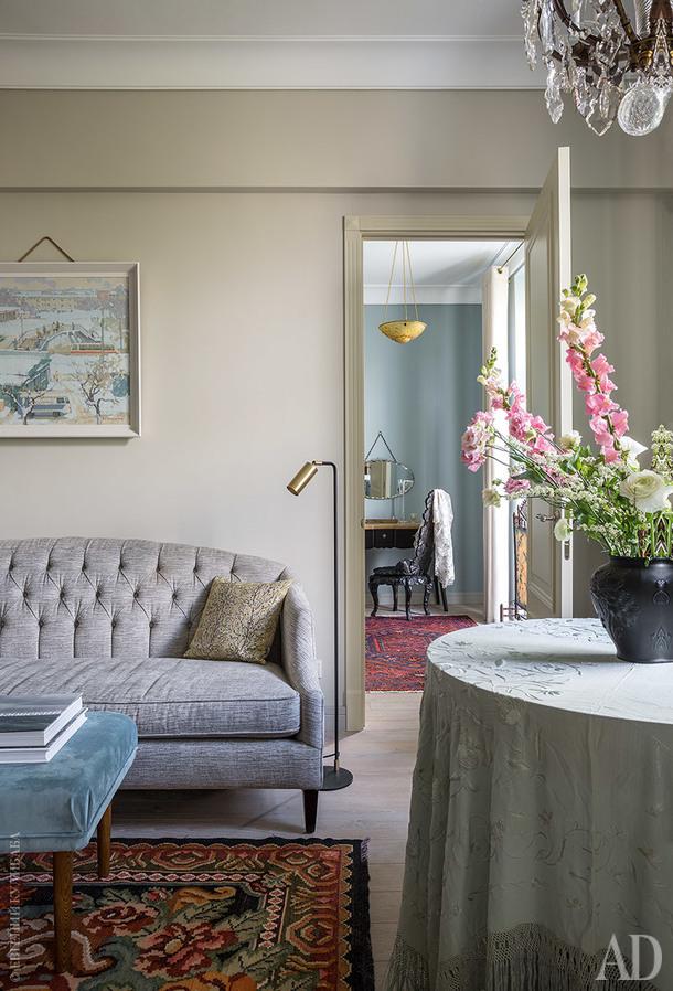 Вид из гостиной на спальню. На переднем плане стол под французской вышитой шалью начала ХХ века и диван, Bernhardt. В спальне французская люстра из цветного стекла и резной стул начала ХХ века, антикварное английское зеркало и туалетный столик, LRoom. Ковер, Ikea.