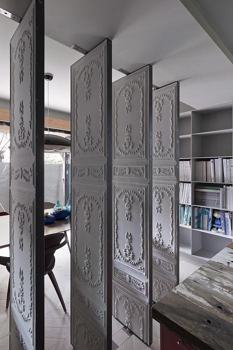 Поворотная перегородка из гипса, украшенная фантастической лепниной, которую можно в любой момент превратить в обыкновенную стену.