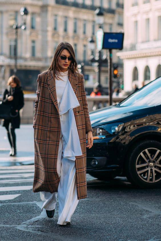 Девушка в легких белых брюках, коричневое пальто в клетку
