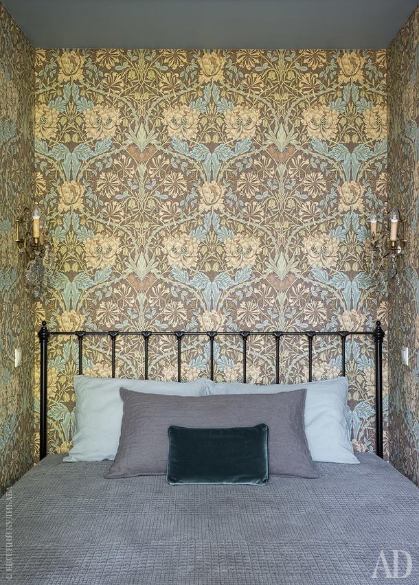 Спальня хозяйки. Сделанная на заказ кованая кровать встала в нишу, образованную парой встроенных шкафов. Стены оклеены обоями по дизайну Уильяма Морриса. На стене пара шведских бра XIX века, их купили на аукционе. Покрывало, Zara Home.