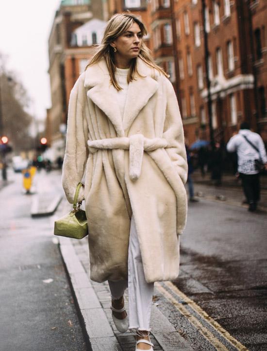Девушка в плюшевой бежевой шубе, белые брюки и маленькая сумочка