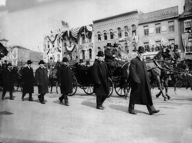 Агенты секретной службы ходят по обеим сторонам экипажа президента Теодора Рузвельта во время его инаугурации 4 марта 1905 года. Он был первым президентом, которому была предоставлена защита секретной службы.