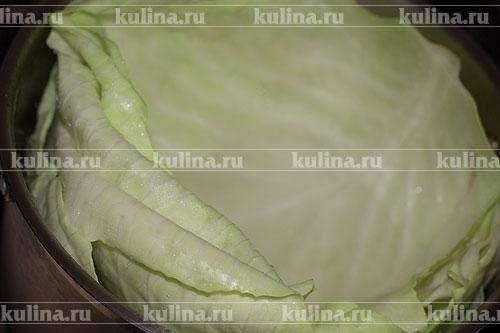 Снять с кочана 5 капустных листьев, положить их в большую кастрюлю и бланшировать в горячей воде 10 минут, затем воду слить.