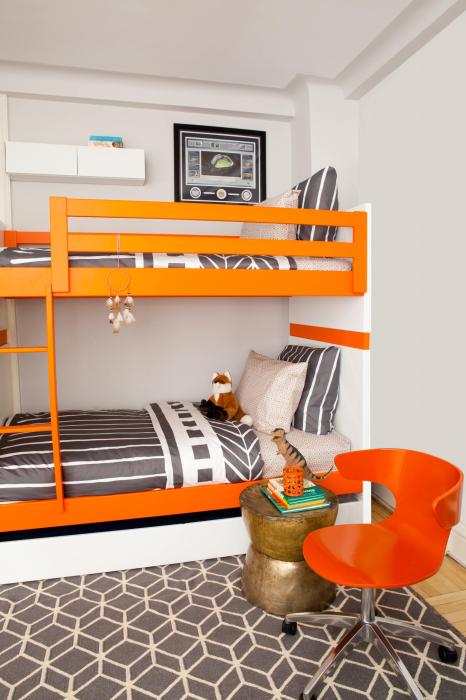 Небольшая спальная комната в светлых тонах с необычной встроенной деревянной конструкцией, которая включает в себя два спальных места.