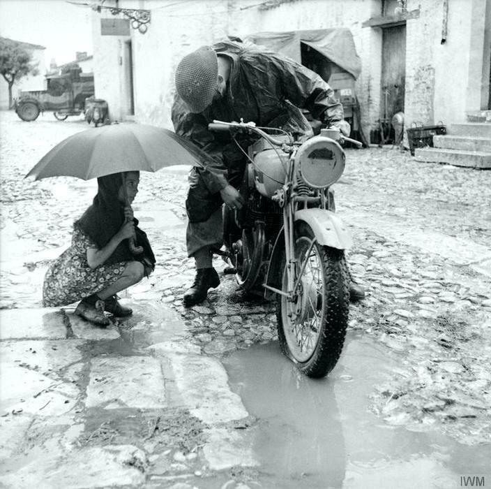 Маленькая девочка с зонтиком наблюдает за попыткой британского гонщика отремонтировать карбюратор мотоцикла под проливным дождем. Италия. 4 октября 1943 года