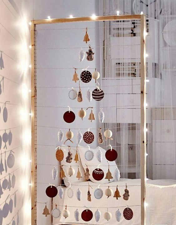 27 take a large frame hang some yarn and form a Christmas tree of your favorite ornaments line it up with lights