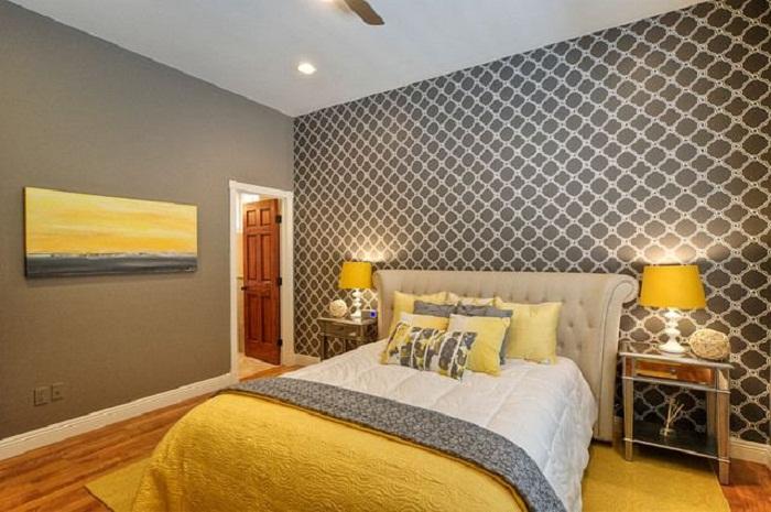 Крупный геометрический принт на одной стене сделает площадь спальни больше.