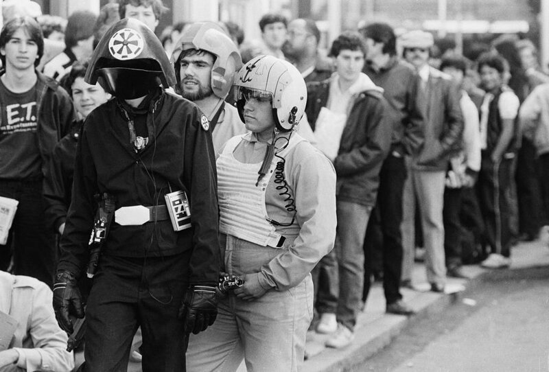 Три костюмированных фаната стоят в очереди, чтобы купить билеты на премьеру «Возвращения джедая» возле Бостонского театра 25 мая 1983 года