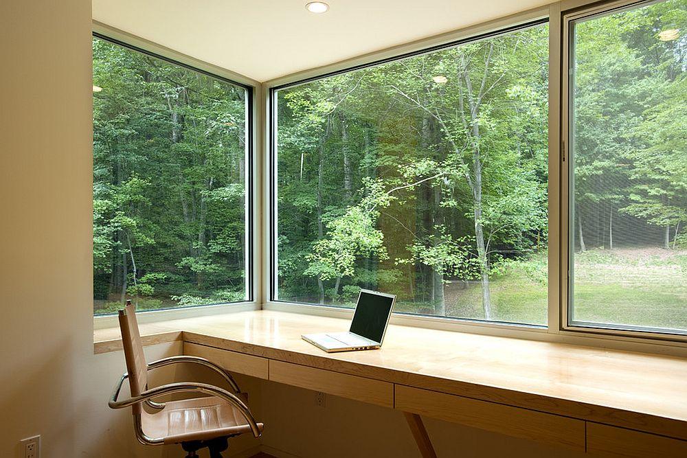 Большие окна в домашнем мини-офисе с видом на лес