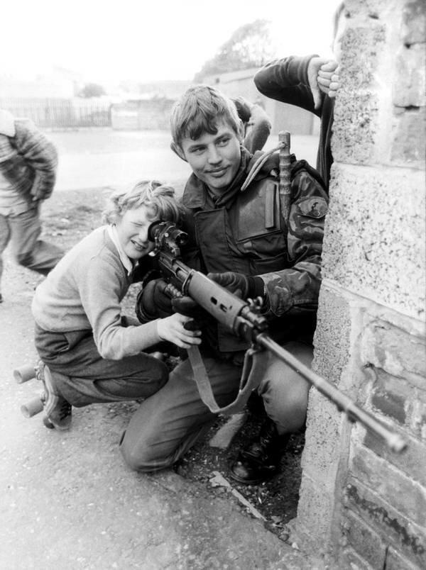 Британский солдат позволяет мальчику взглянуть на прицел в Белфасте, 1981 год.