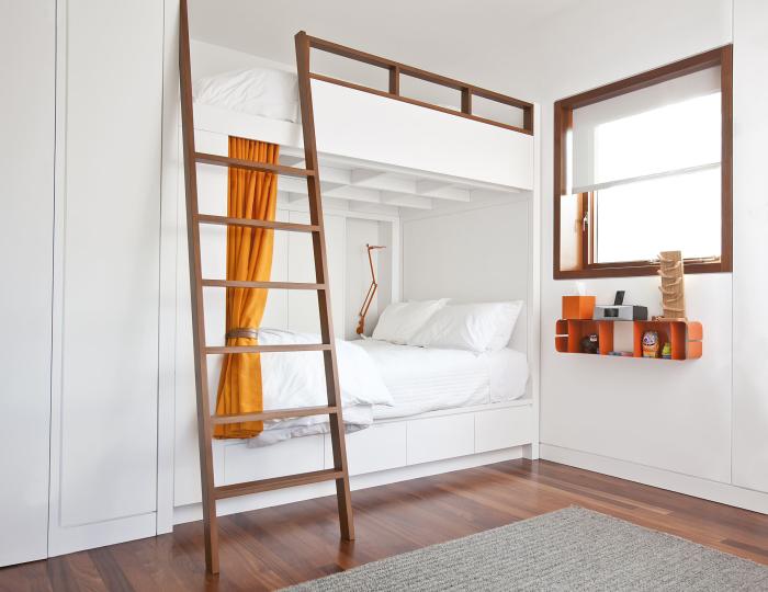 Небольшая уютная спальная комната с белыми стенами и двухэтажной кроватью с выдвижными ящиками.