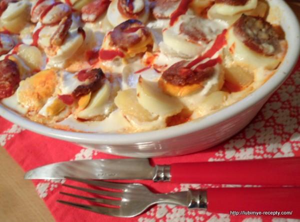 Картофель, запечёный слоями с колбасками и яйцами в сметане.
