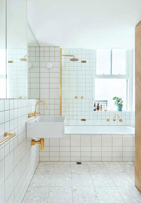 Белый кафель и большие зеркала сделали ванную комнату светлой и просторной. | Фото: interiorizm.com.