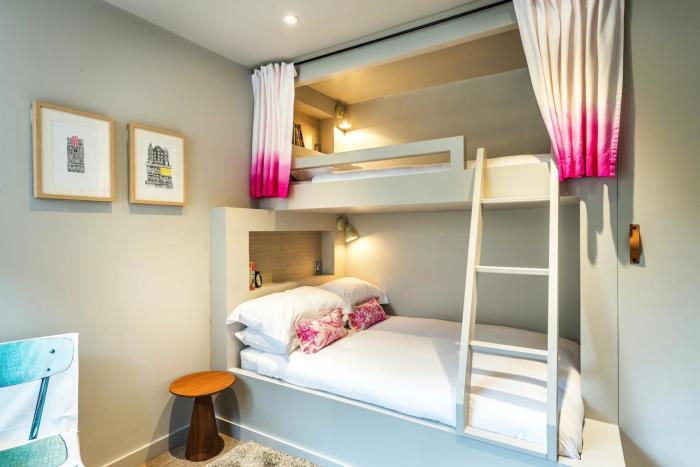 При выборе многоярусной кровати в небольшой спальне стоит обратить внимание на наличие встроенных систем хранения.