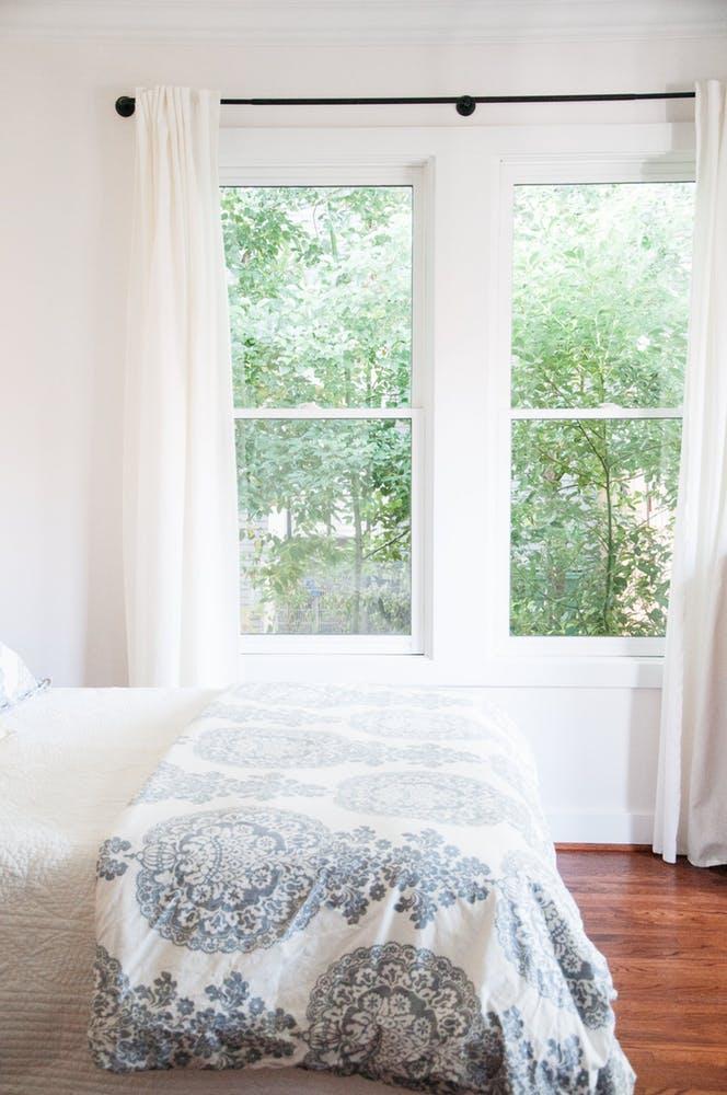 Элегантный интерьер белой спальни с большим окном