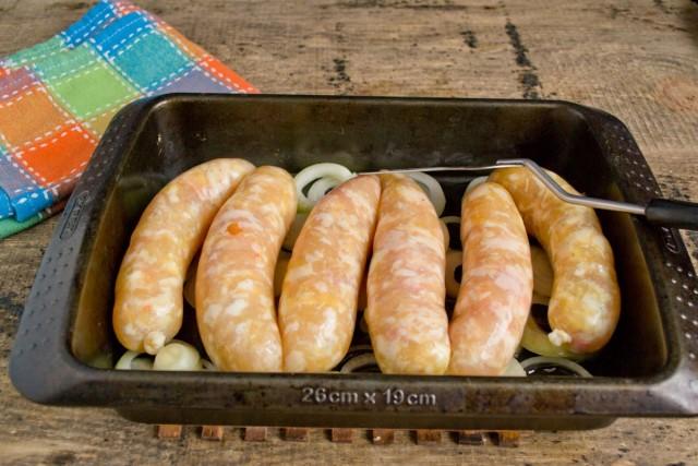 На лук кладём колбаски в один ряд