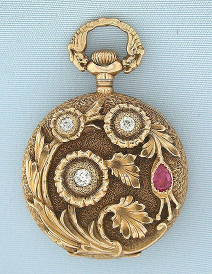 Beautiful Gruen 14K gold, diamond, and ruby beautifully decorated ladies antique pendant watch circa 1900. The case with overall engraving, the back with a high relief spray of flowers set with diamonds and a ruby. Unusual bow with mythical beasts. White enamel dial (minor hairlines) with red and gold numbers, gold and silver minute markers, and blued steel hands. Nickel 16 jewel adjusted movement.: