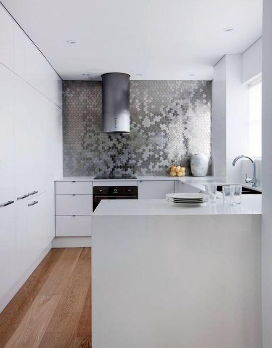 Небольшая кухня с акцентной стеной, отделанной зеркальной плиткой.