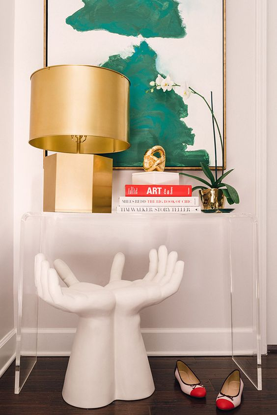 18 console table styled with a sculpture a gold lamp and an oversized wall art