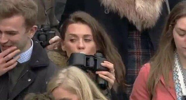 Оператор канала ITV Racing заснял, как девушка быстро оглядывается, откручивает крышку бинокля и осторожно подносит его ко рту Челтнем, алкоголь, бинокль, великобритания, гонка, зритель, спорт, фляга