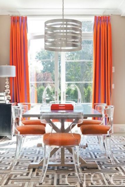 12 modern lucite chairs with orange upholstery make a cool statement in this dining room