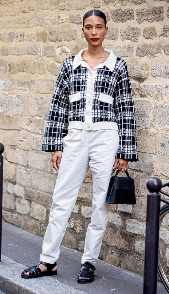 Девушка в белых джинсах, серый жакет в клетку и черные сандалии