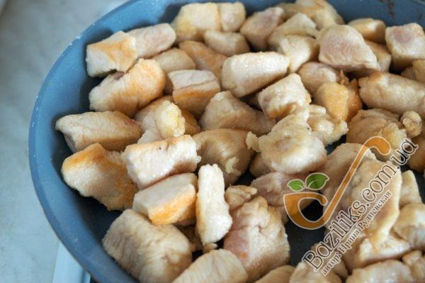 Хорошо разогреваем сковороду или вок и добавляем оливковое масло. Выкладываем кусочки куриного филе в муке и подрумяниваем его со всех сторон, периодически переворачивая курицу лопаткой или встряхивая вок. Делаем это очень быстро, чтобы не пересушить курицу и она оставалась сочной. Румяные кусочки курицы перекладываем в тарелку и накрываем фольгой, чтобы курица оставалась теплой.