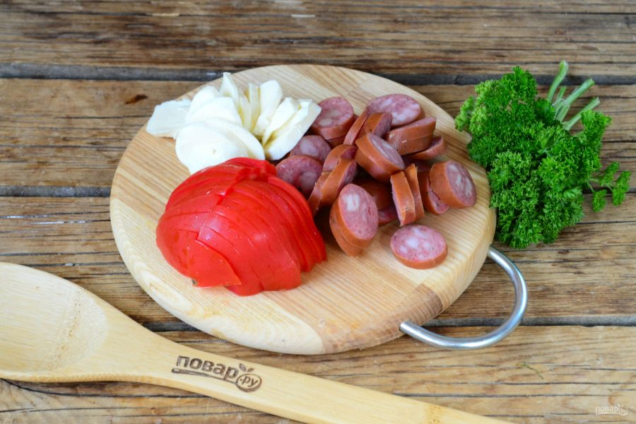 Помидор, охотничьи колбаски и моцареллу нарежьте небольшими ломтиками.