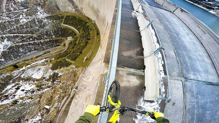 А ты знаешь, что такое безумие? 21-летний экстремал балансирует на своём велосипеде на перилах 200-метровой дамбы