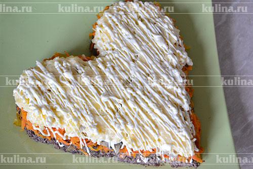 Затем приступаем к украшению праздничного салата. Покрываем сырный слой тонкой сеткой майонеза.