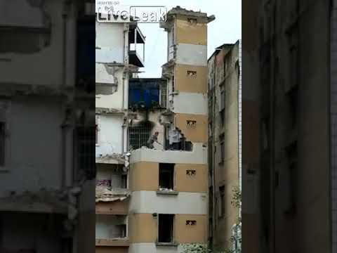Мужчина разрушает здание кувалдой