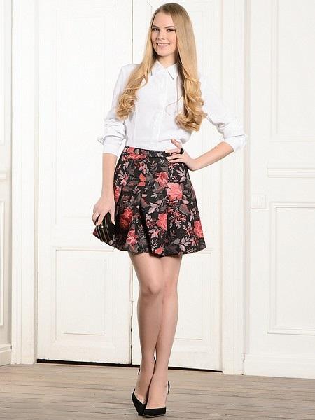 Девушка в белой блузке и цветочной короткой юбке