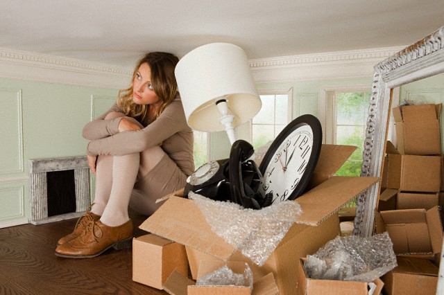 Young woman with box of objects in small room --- Image by © Image Source/Corbis