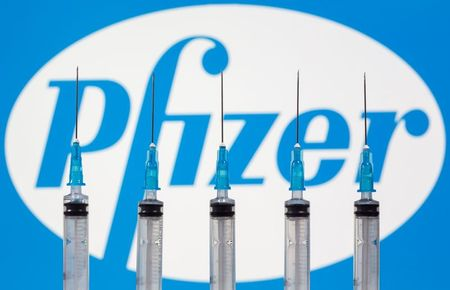 Syringes are seen in front of a displayed Pfizer logo in this illustration taken, November 10, 2020. REUTERS/Dado Ruvic/Illustration