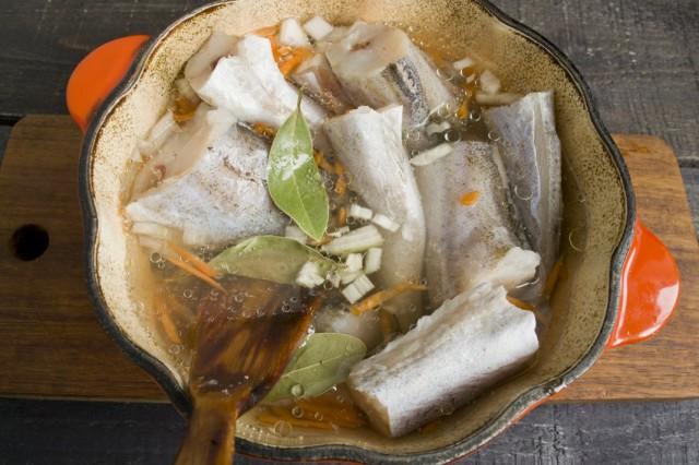 В кастрюлю кладём сливочное масло, закладываем репчатый лук, морковь, сверху кладём рыбу и специи. Заливаем холодной водой