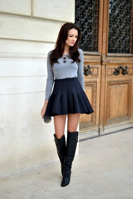 Девушкав короткой черной юбке и черных ботфортах