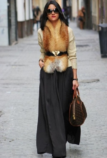 Девушка в меховом жилете и широкой юбке макси