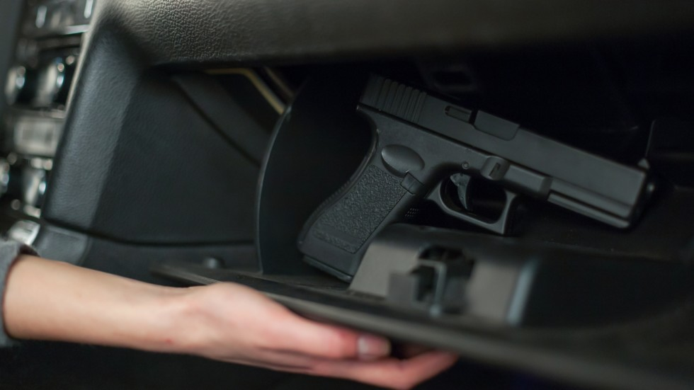 The female hand pulls out a gun from the glove box in the car.