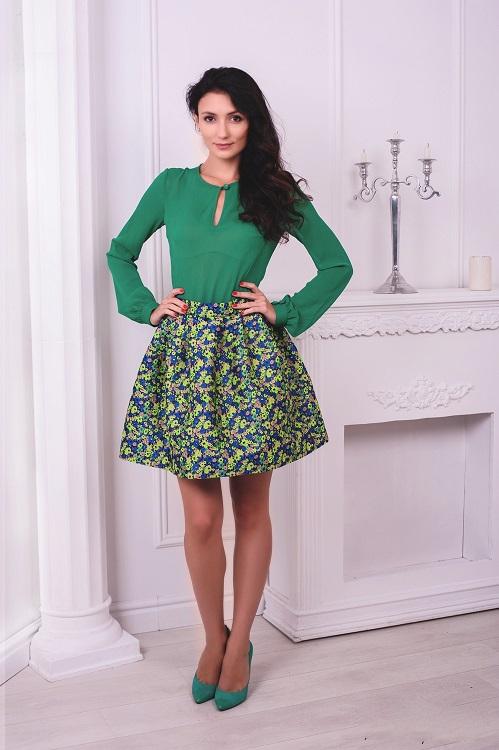Девушка в короткой, широкой юбке и зеленой блузке