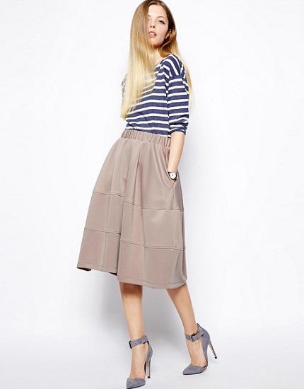 Девушка в юбке миди и полосатой водолазке