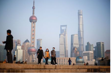 People walk at the Bund, in front of Lujiazui financial district of Pudong, on the day of the opening session of the Chinese People's Political Consultative Conference (CPPCC), in Shanghai, China March 4, 2021.  <div id=