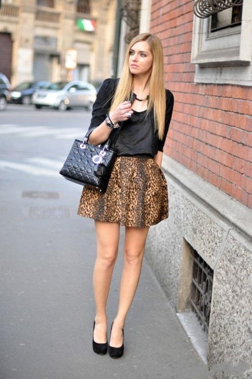 Девушка в короткой леопардовой юбке и черной блузке