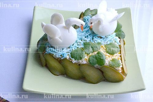 Отправляем сформированных лебедей на вершину салата. Отложенные белки, окрасив соком синей капусты в голубой цвет, выкладываем рядом с лебедями. Можно ещё положить несколько листиков зелени.