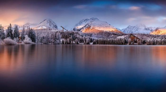 Переливы воды и солнечного света создают впечатление северного сияния на озере.