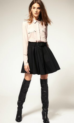 Девушка в короткой черной юбке и ботфортах