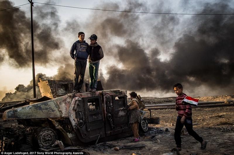11-летний Таха Сирхах идет с иракским флагом по выжженному месторождению нефти, город Кайяра в мире, дети, жизнь